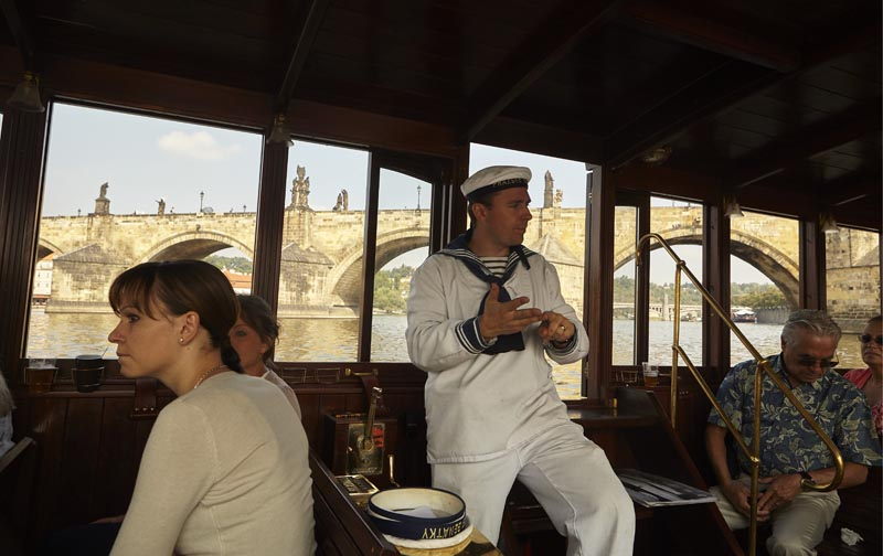 The ship's captain on the ship tells the history of the Charles Bridge